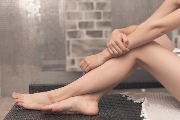 Close-up of woman's feet relaxing on lounge chair in spa