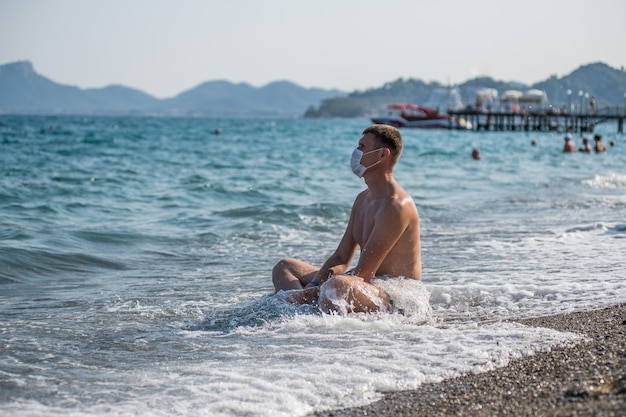 Premium Photo | A man sits alone in the sea and a mask during the covid 19  flu epidemic