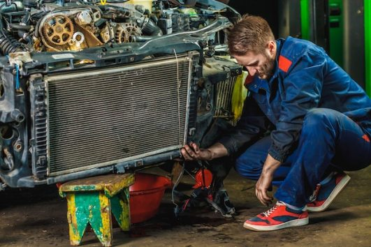 Premium Photo | A tired mechanic in a blue protective suit is repairing a car radiator. repair service concept.