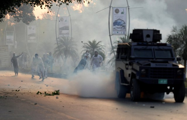 Protesters hurl stones at an armored vehicle after police fired tear gas shells to disperse a march toward the French Embassy at a rally against French President Macron. Islamabad, Pakistan. Oct. 30, 2020