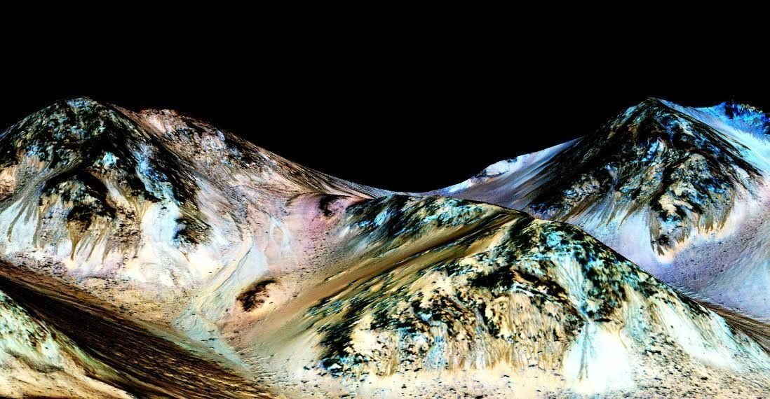 """<span class='image-component__caption' itemprop=""""caption"""">The dark streaks are known as recurring slope lineae and are believed to be evidence of flowing water. The blue color seen upslope of the dark streaks is thought not to be related to the streaks but to the presence of the mineral pyroxene.</span>"""