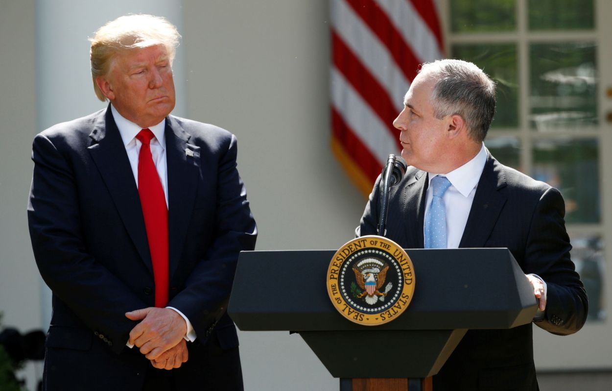 President Donald Trump listens to Scott Pruitt in the White House Rose Garden after announcing his decision to leave the Pari