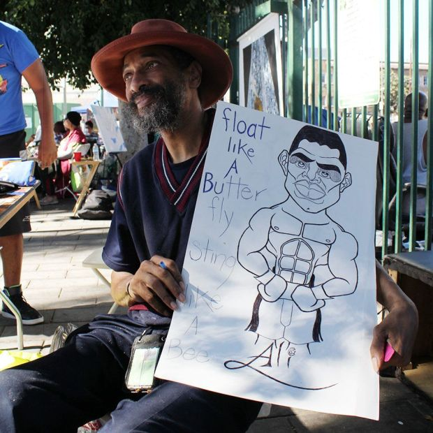 Former animation artist Robert Tolbert is seen with a picture he drew of one of his heroes, Muhammad Ali.