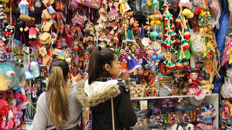 Young girls look at toys in El Mercado.