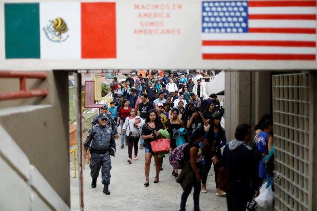 Caravan members walk toward the United States border and customs facility.