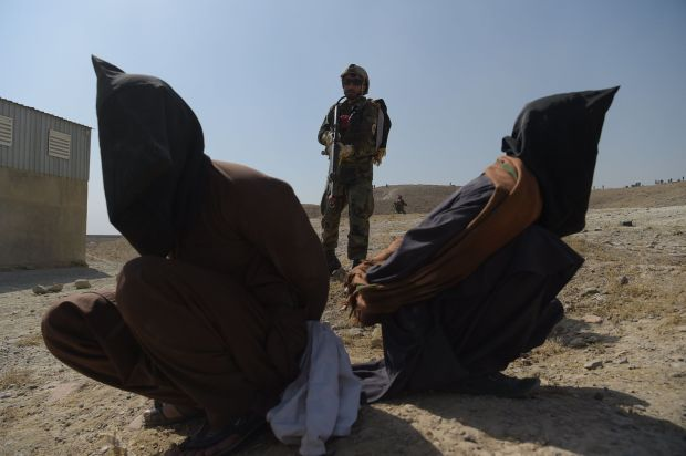 An Afghan National Army commando arrests men pretending to be Taliban fighters during a military exercise at the Kabul Milita