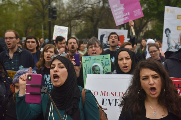 Demonstrators gather outside the United States Supreme Court as the court hears a case involving the travel ban on April 25.