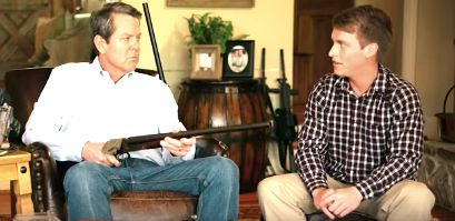 "Republican Brian Kemp points a shotgun at ""Jake"" on his political ad for the Georgia governor's race."