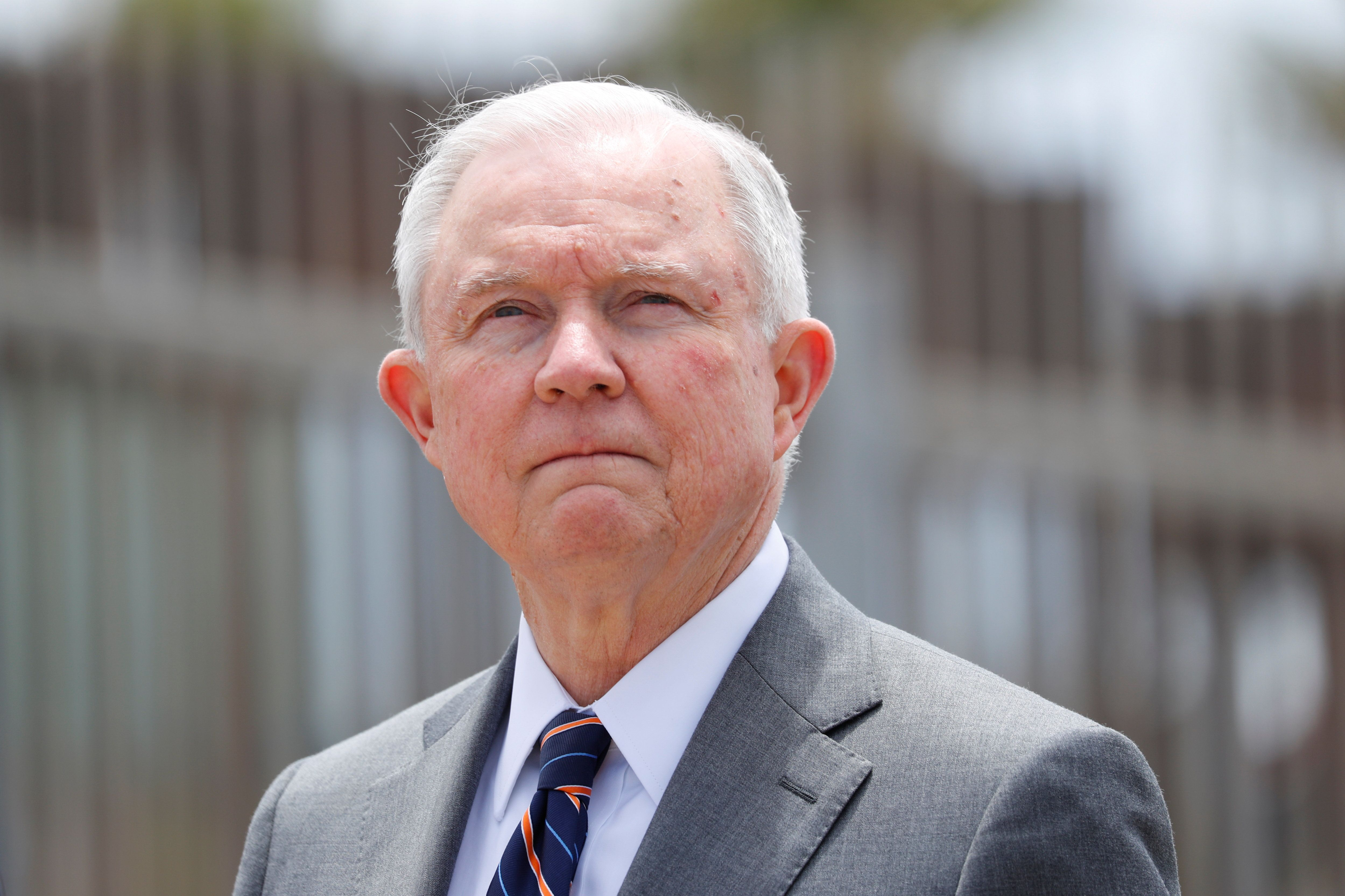 Attorney General Jeff Sessions stands next to the border fence near San Diego on May 7 as he discusses immigration enforcemen