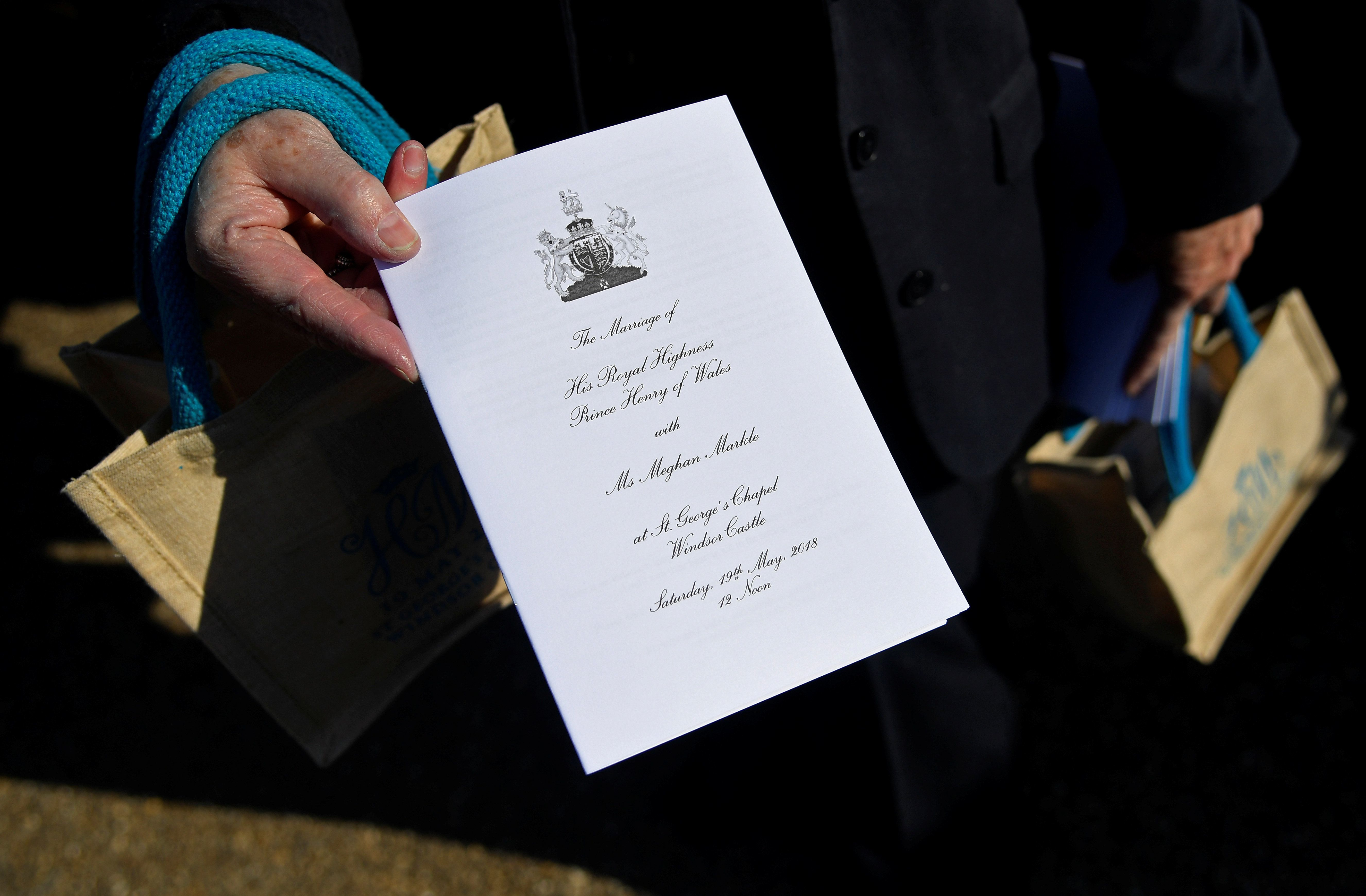 A member of staff holds a service sheet and goodie bags ahead of the wedding of Britain's Prince Harry to Meghan Markle.