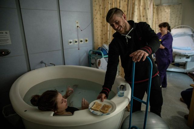 Damien Armes gives his wife Tamzin Lines slices of toast as she sits in a birthing pool in the maternity ward of the Royal De