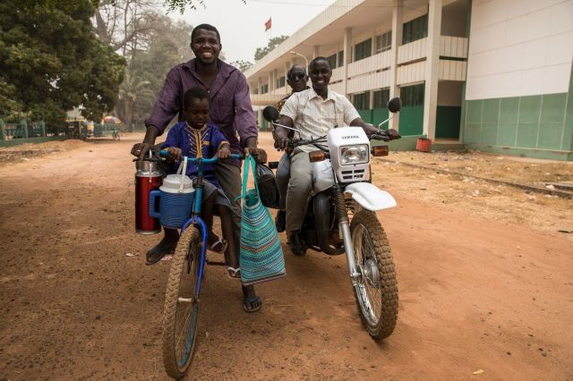Mamudo Queta, sitting astride a bicycle with 4-year-old Moustapha, heads back to the hospital with food for his wife.