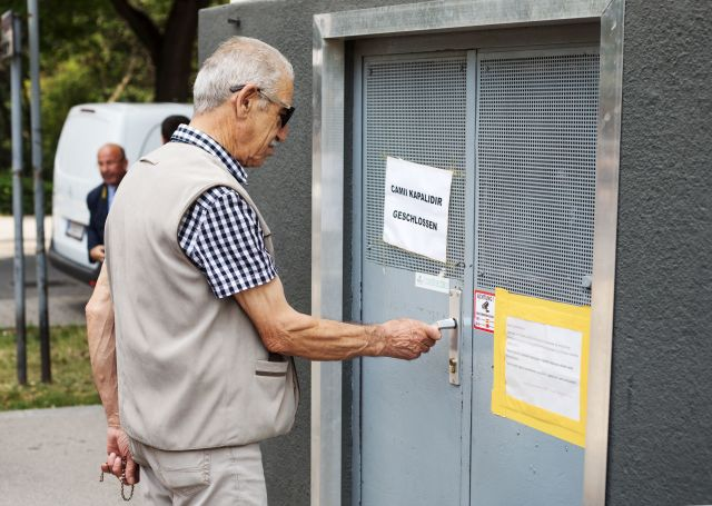 A community member tries to open the door of the 'Nizam-i Alem' mosque in Vienna's 10th district, on June 8, 2018. The mosque