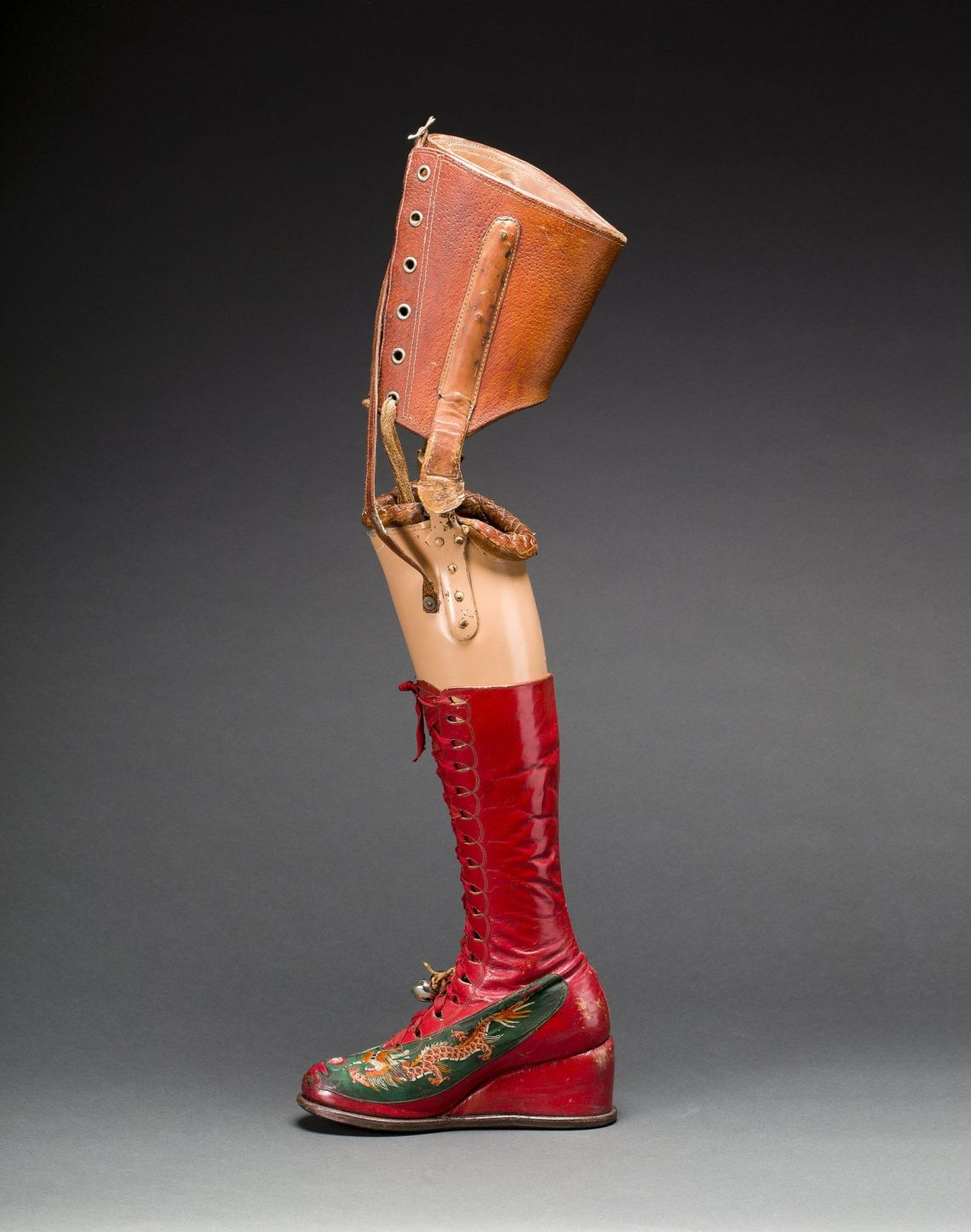 Prosthetic leg with leather boot. Appliquéd silk with embroidered Chinese motifs.