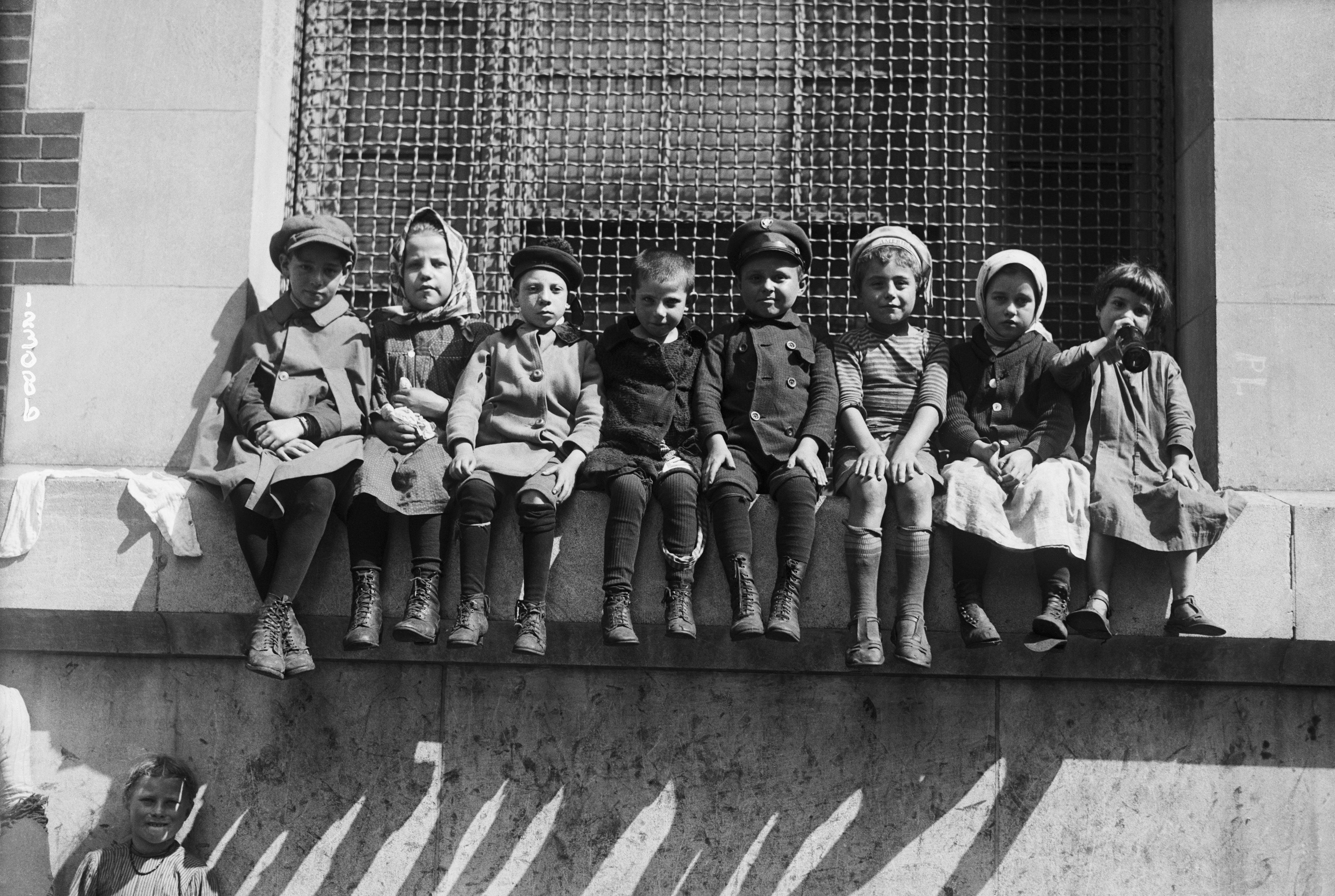 Children sit on a window ledge atan overcrowded immigration station at Ellis Island a century ago.Whenfamil