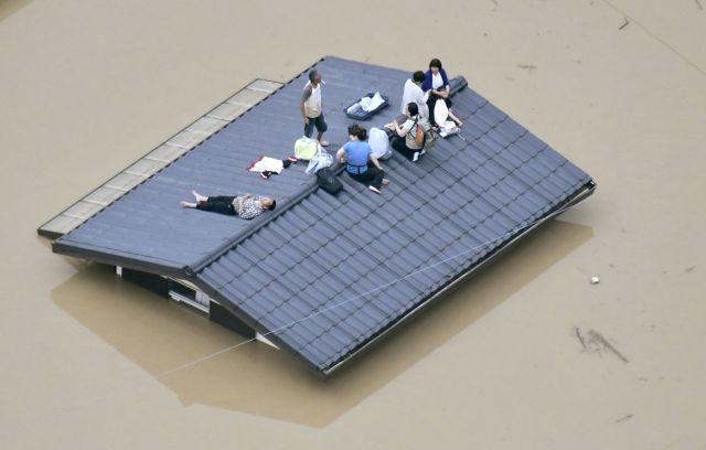 An aerial view shows local residents on the roof of a submerged house in a flooded area as they wait to be rescued