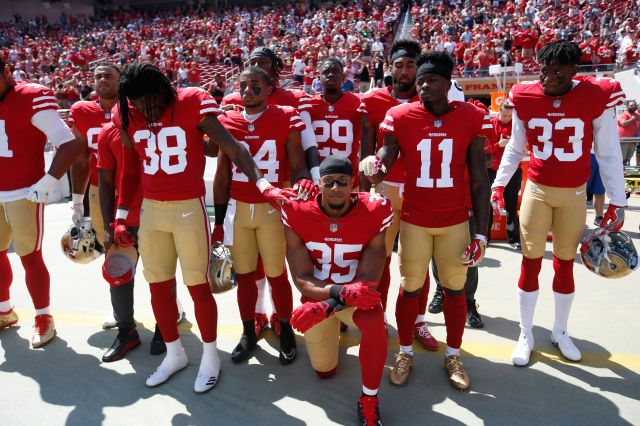"Eric Reid of the San Francisco 49ers leads the team in a ""call to attention"" during the playing of the national anthem before"