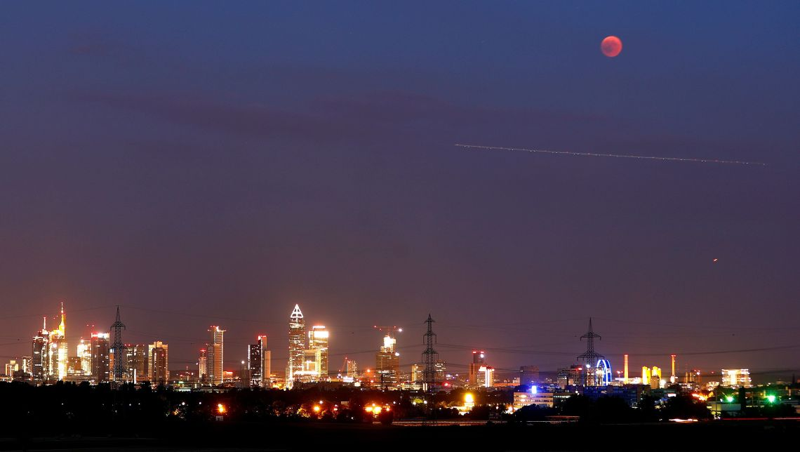 A blood moon is seen in the sky over the skyline of Frankfurt as an airplane passes by, Germany, July 27, 2018. Picture taken with long exposure.