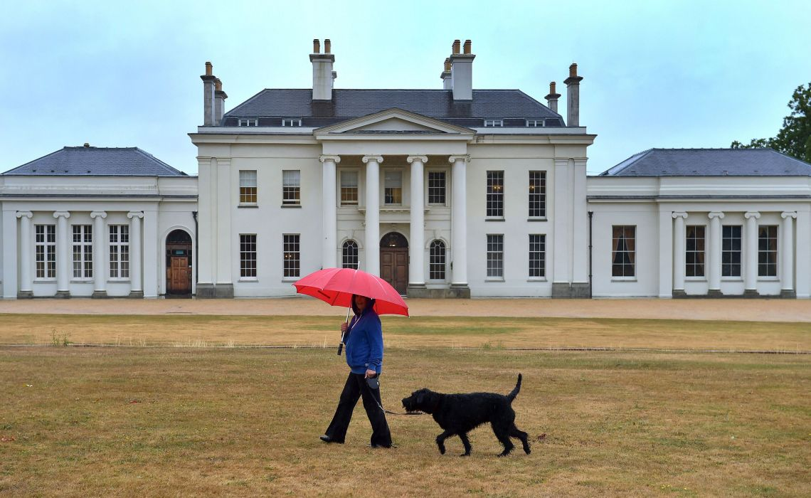A woman walks her dog past Hylands House at Hylands Park in Chelmsford, Essex, on Sunday.