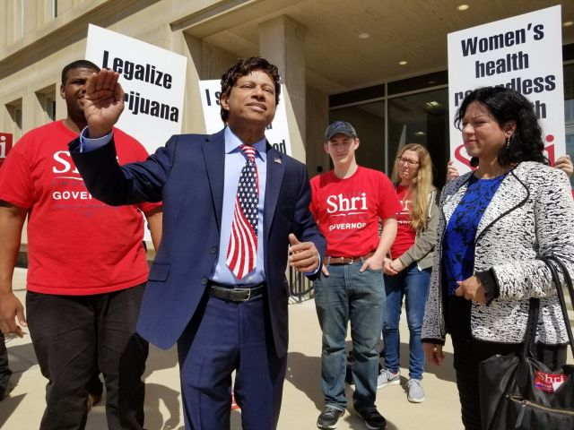 "Shri Thanedar stands with supporters at a campaign event in April. He calls himself the ""most progressive"" Democrat in Michig"