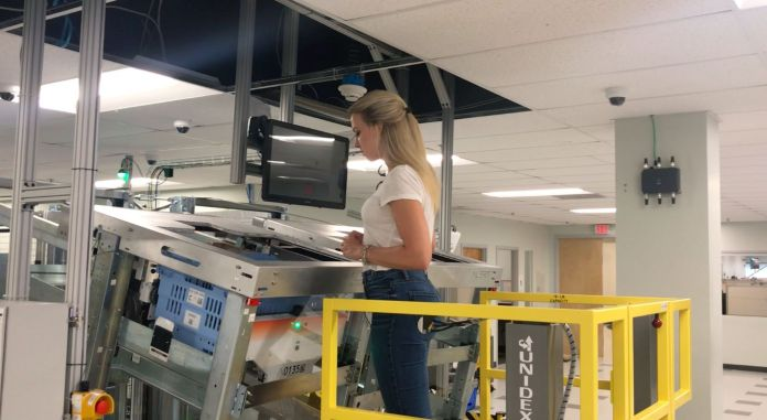 Yahoo Finance reporter Julia La Roche observes the Alphabot in action at Alert Innovation.