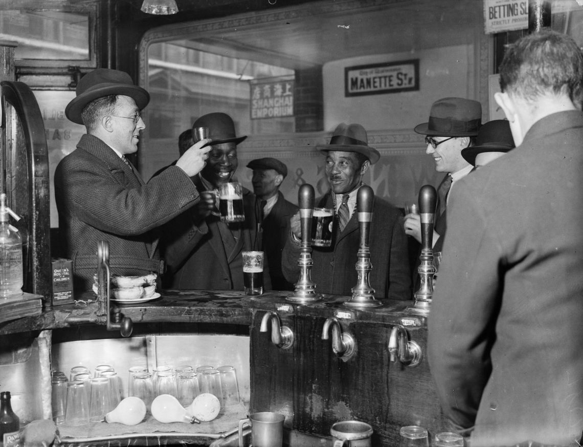The original photograph of customers raising a glass inside the Pillars of Hercules pub in Soho in November 1933.