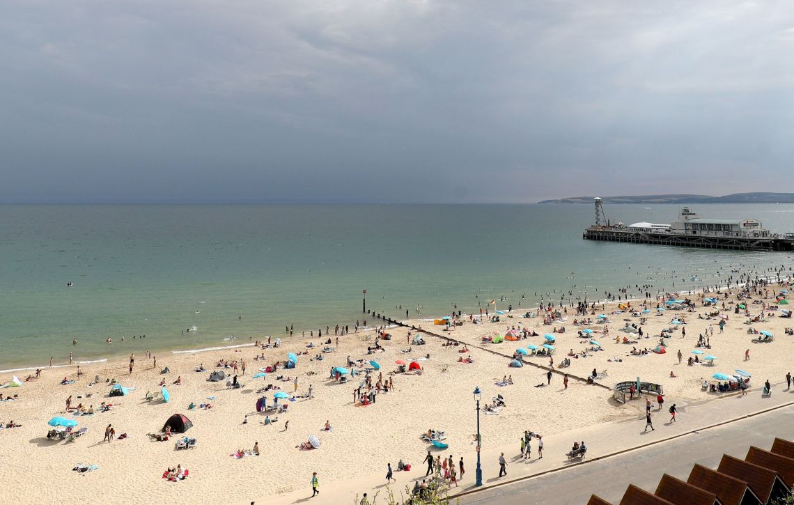 Storm clouds gather out at sea as people enjoy the warm weather on Bournemouth beach on Tuesday.