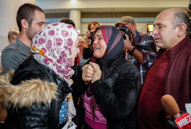 Syrian refugee Baraa Haj Khalaf (left) reacts as her mother Fattoum (center) cries and her father Khaled (right) looks on aft