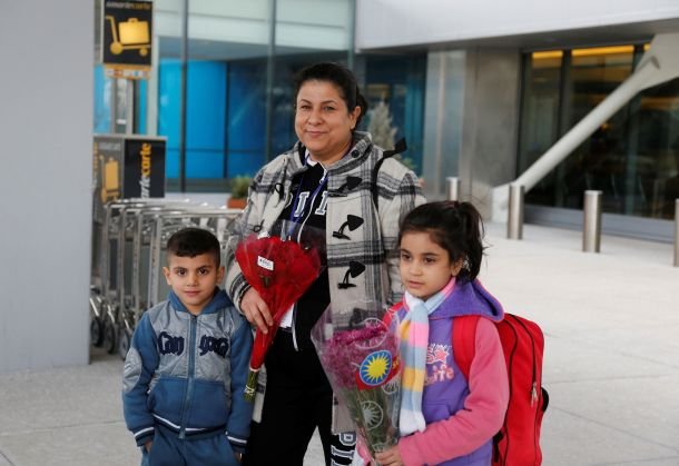 Iraqi refugee Amira Al-Qassab stands outside with two of her children as a relative picks them up at Detroit Metro Airport in