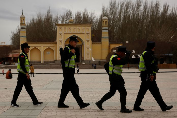A police patrol walks in front of the Id Kah Mosque in the old city of Kashgar, Xinjiang Uighur Autonomous Region, China, Mar