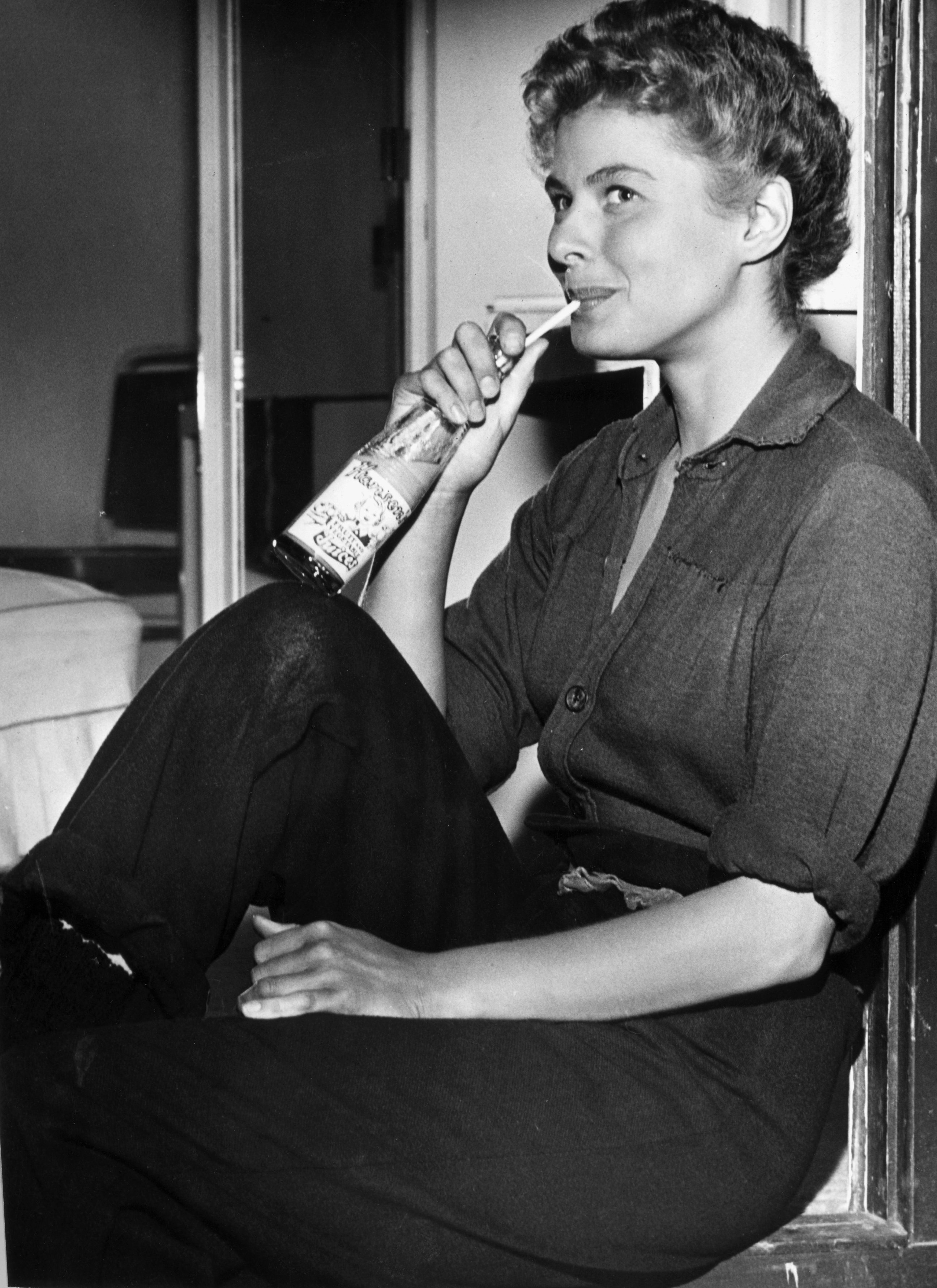 The actress sitting on a window ledge, sipping juice from a glass bottle with a straw, on the set of director Sam Wood's film