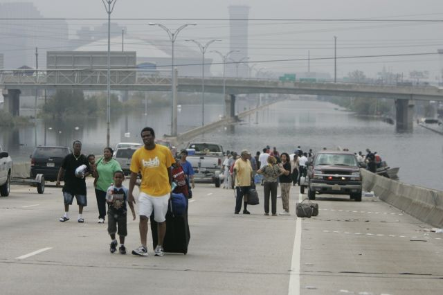 Residents of New Orleans rescued by police boats walk from floodwaters in front of the Superdome on Sept. 1, 2005.