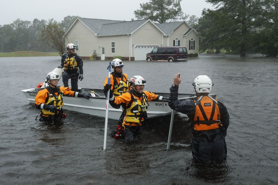 Members of the FEMA Urban Search and Rescue Task Force 4 from Oakland, California, search a flooded neighborhood for evacuees during Hurricane Florence