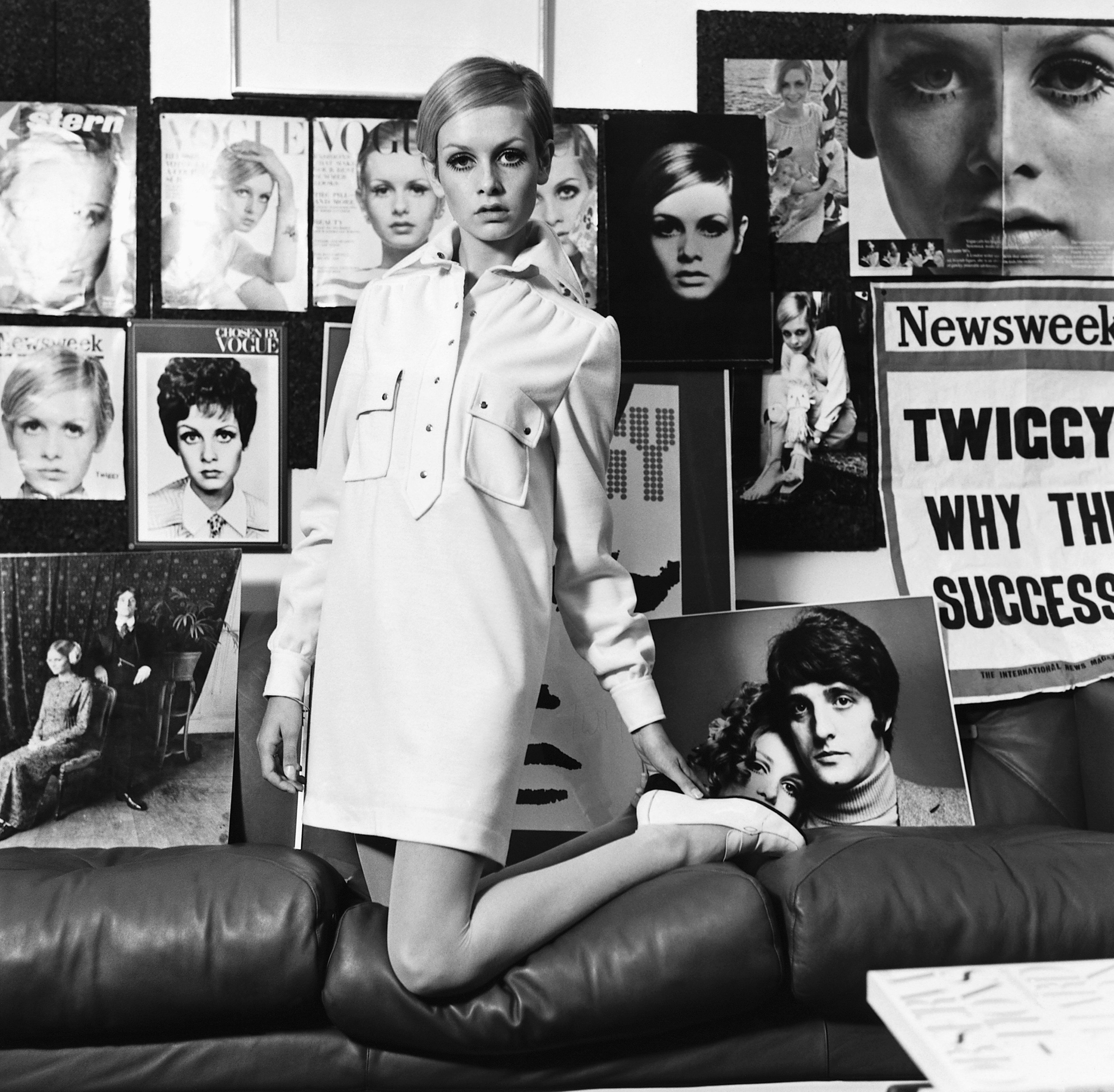 Twiggy models a shirt dress amid posters of her previous work.