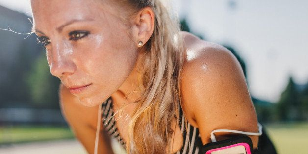 Sweaty, blond haired woman having a rest after hard workout on a sports field.