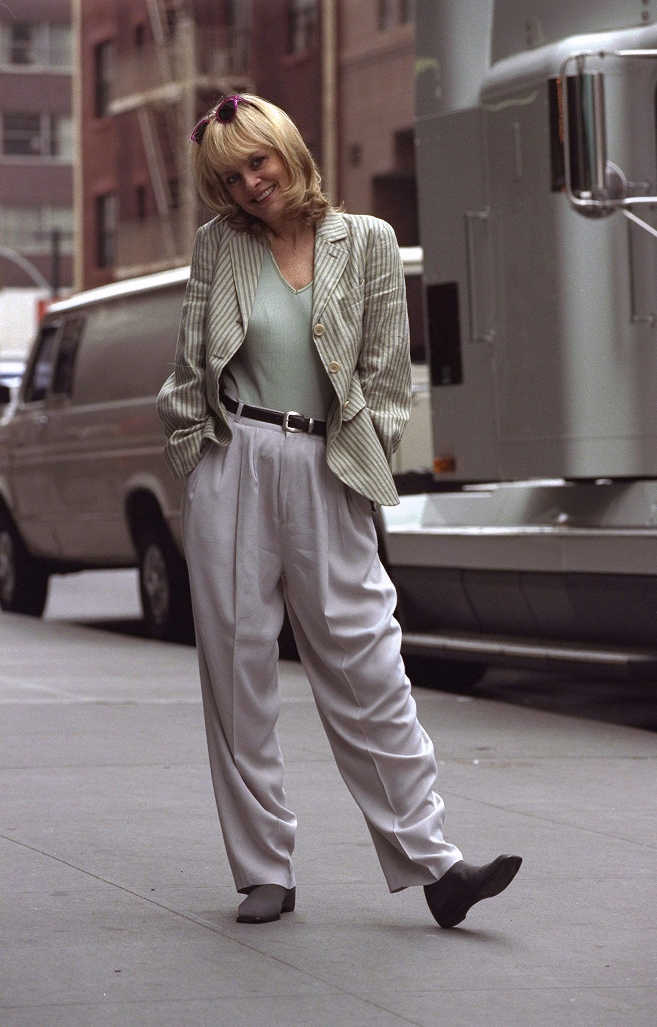 Twiggy posing on the sidewalk in a relaxed outfit.