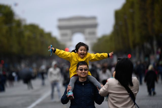 A family poses on the Champs-Elysées on a car-free day in Paris last year.