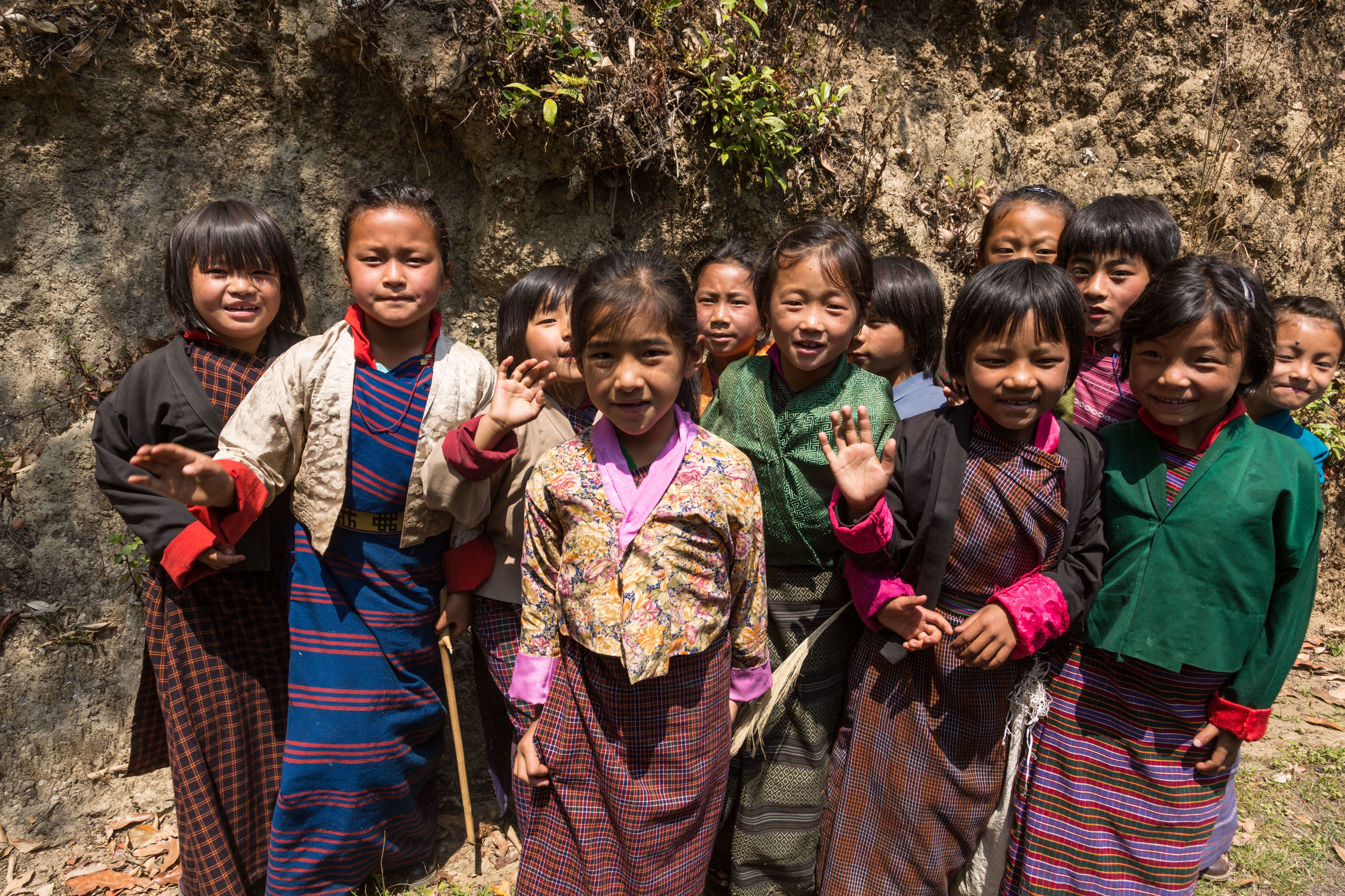 Young schoolgirls in traditional dress pose for their picture by the road in Talo, Bhutan.