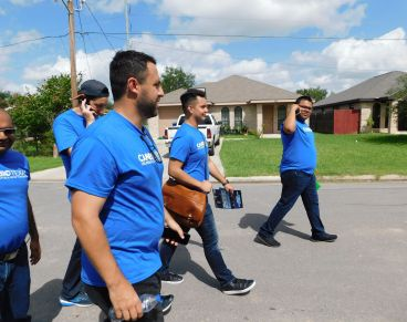 Danny Diaz, in the foreground, leads a group of canvassers to knock on doors in a heavily Hispanic neighborhood of South McAl