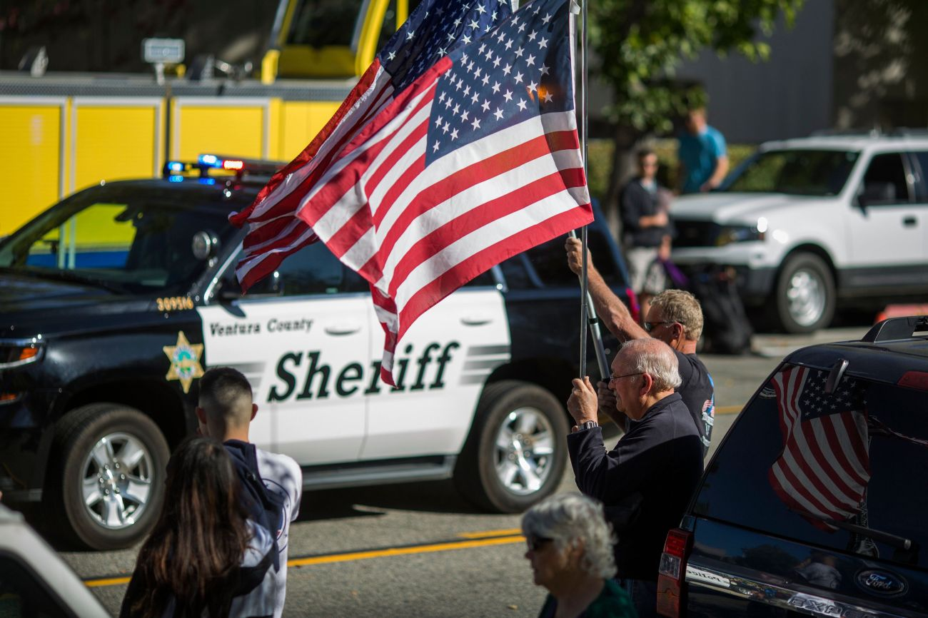 A man waves a flag in Thousand Oaks, California, as a Ventura County Sheriff's patrol car passes. Deputies visited the s