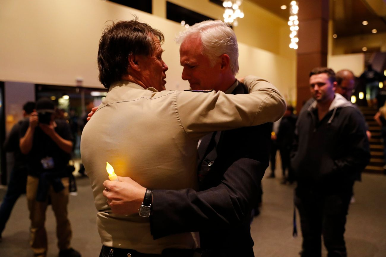 Thousand Oaks Police Chief Tim Hagel, left, hugs Officer Chris Dunn at the vigil.
