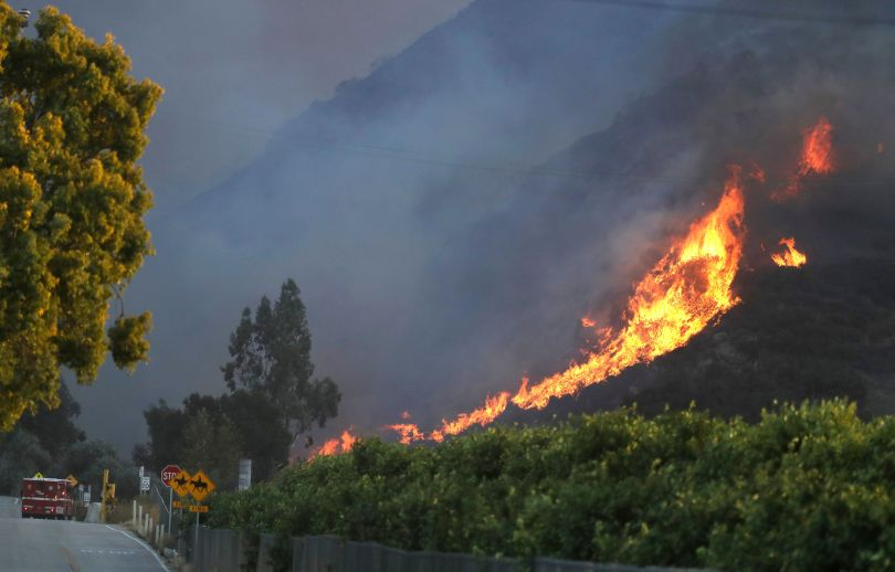 A wildfire comes down from a hilltop near Newbury Park, Calif., on Nov. 8.