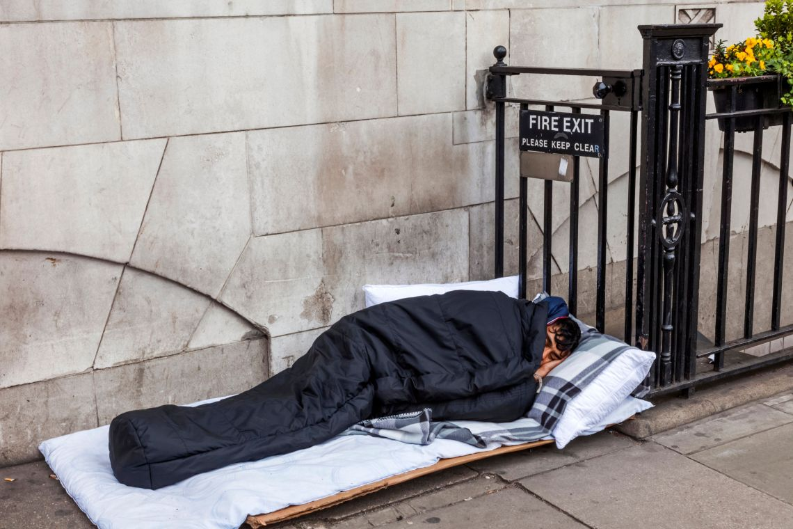 A rough sleeper beds down on the pavement in London