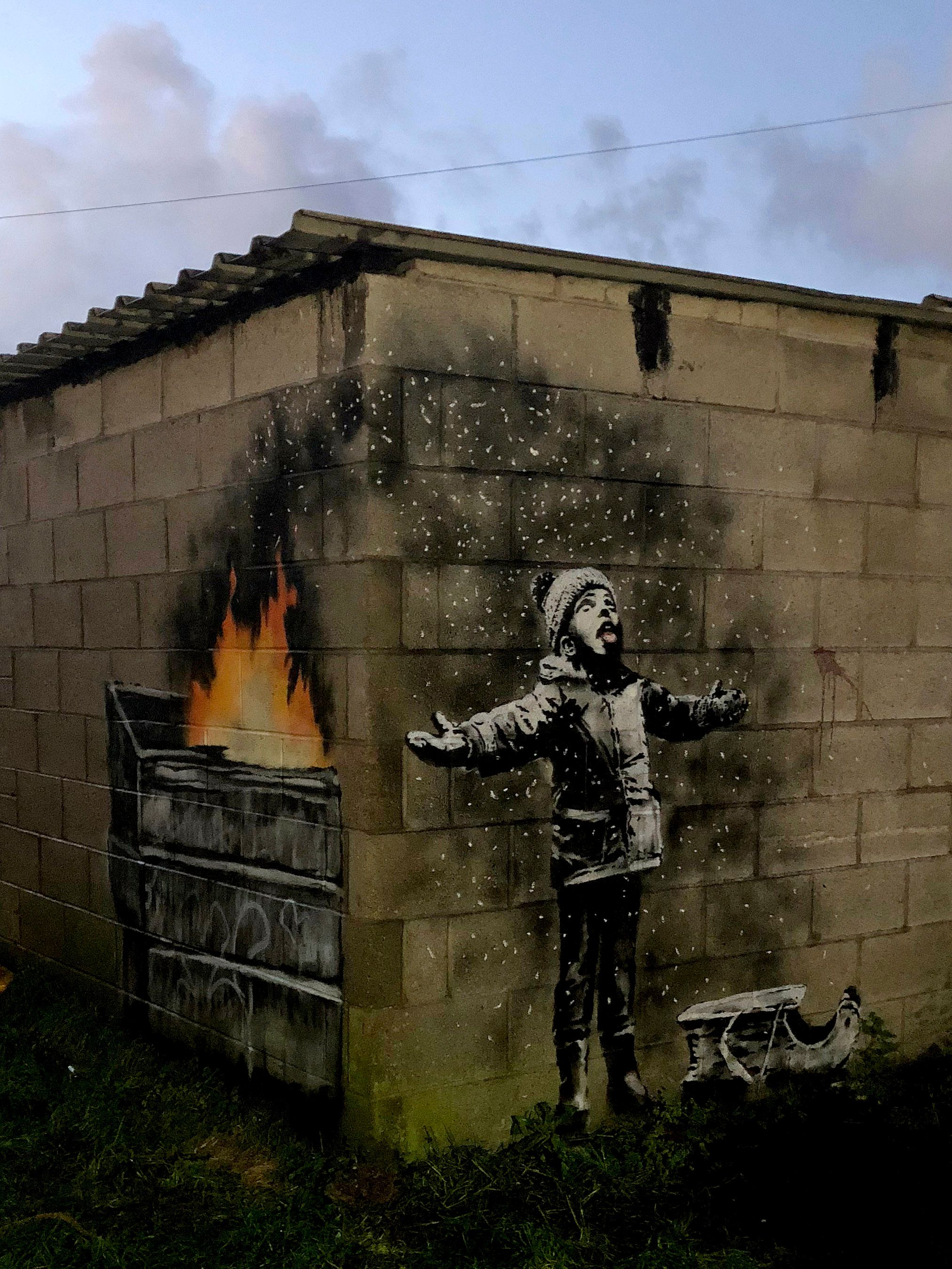 The full mural by Banksy reveals that the child is standing in ash from a dumpster fire.