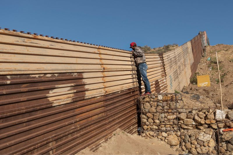 A migrant from Honduras looks from the border fence into the U.S. side to San Diego, Calif., from Tijuana, Mexico.