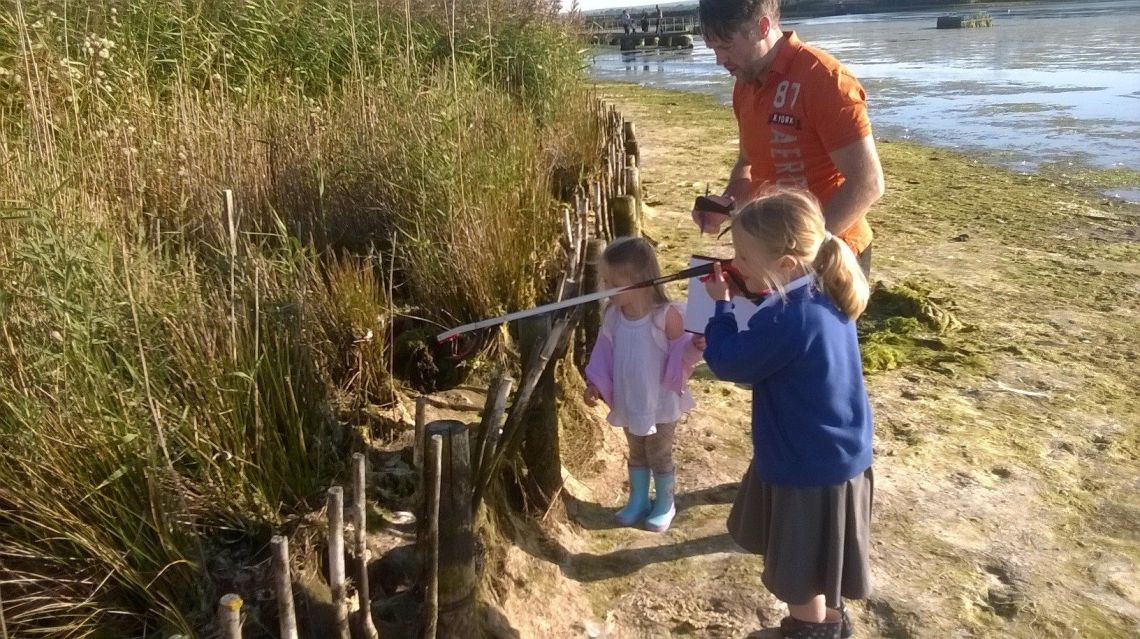 Paul and his daughters doing some litter picking in a drained lake in the park.