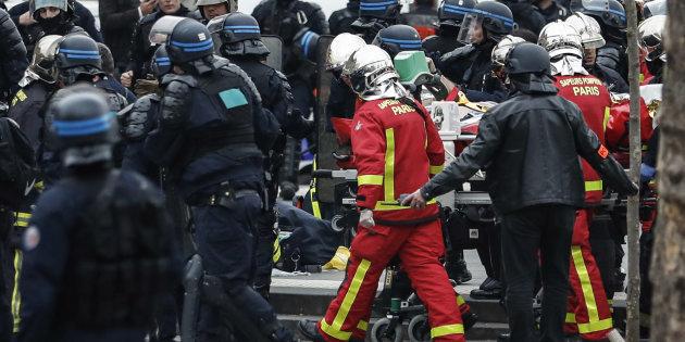 Les pompiers évacuent sur une civière un policier anti-émeute qui s'était effondré sur la place de la...