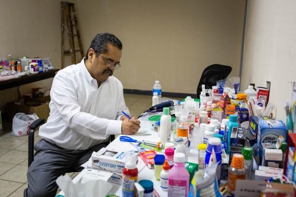 Dr. José Manuel de la Rosa writes a prescription at a makeshift clinic in an old warehouse in El Paso.
