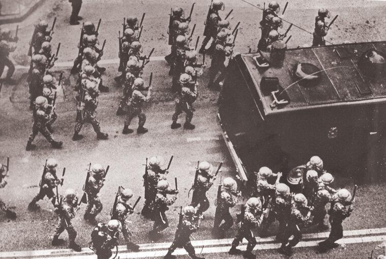 경찰병력이 시위군중에 밀리기 시작하자 금남로에 재투입된 계엄군이 양손에 진압봉을 받쳐들고 시위군중을 향해 전진하고 있다.