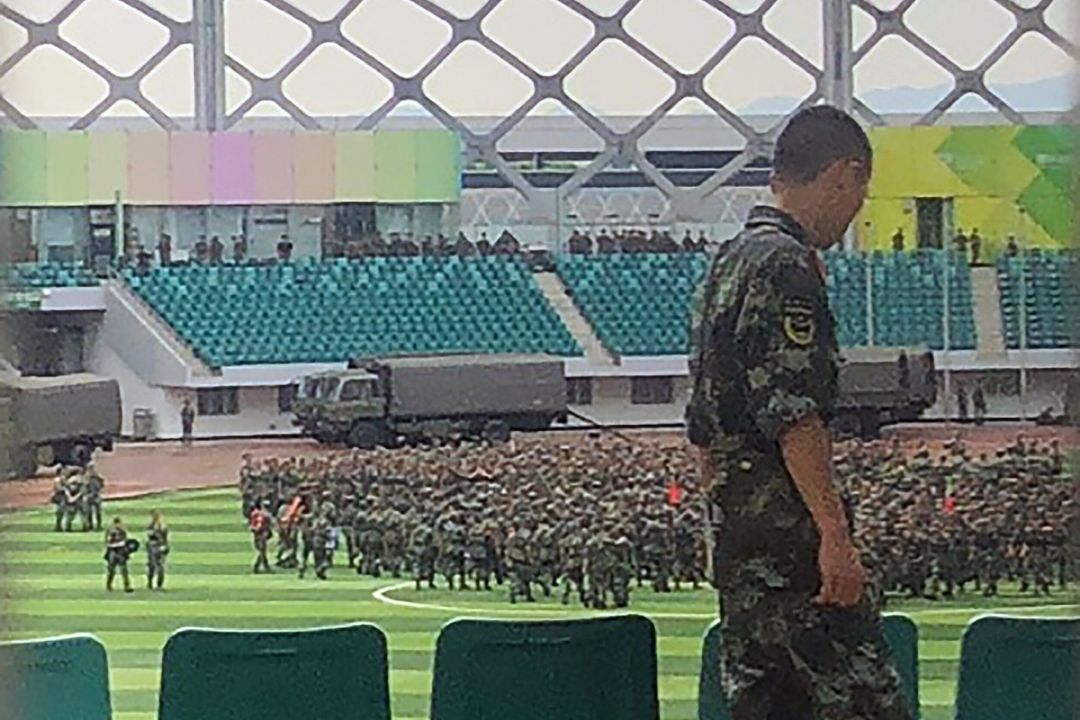 スタジアム内で行進する武装警察